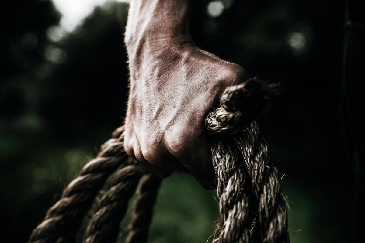 A coil of rope in the hands of a man.