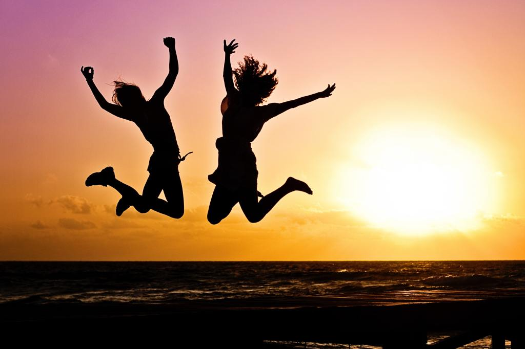 Two ladies jubilating at the shore during sunset.