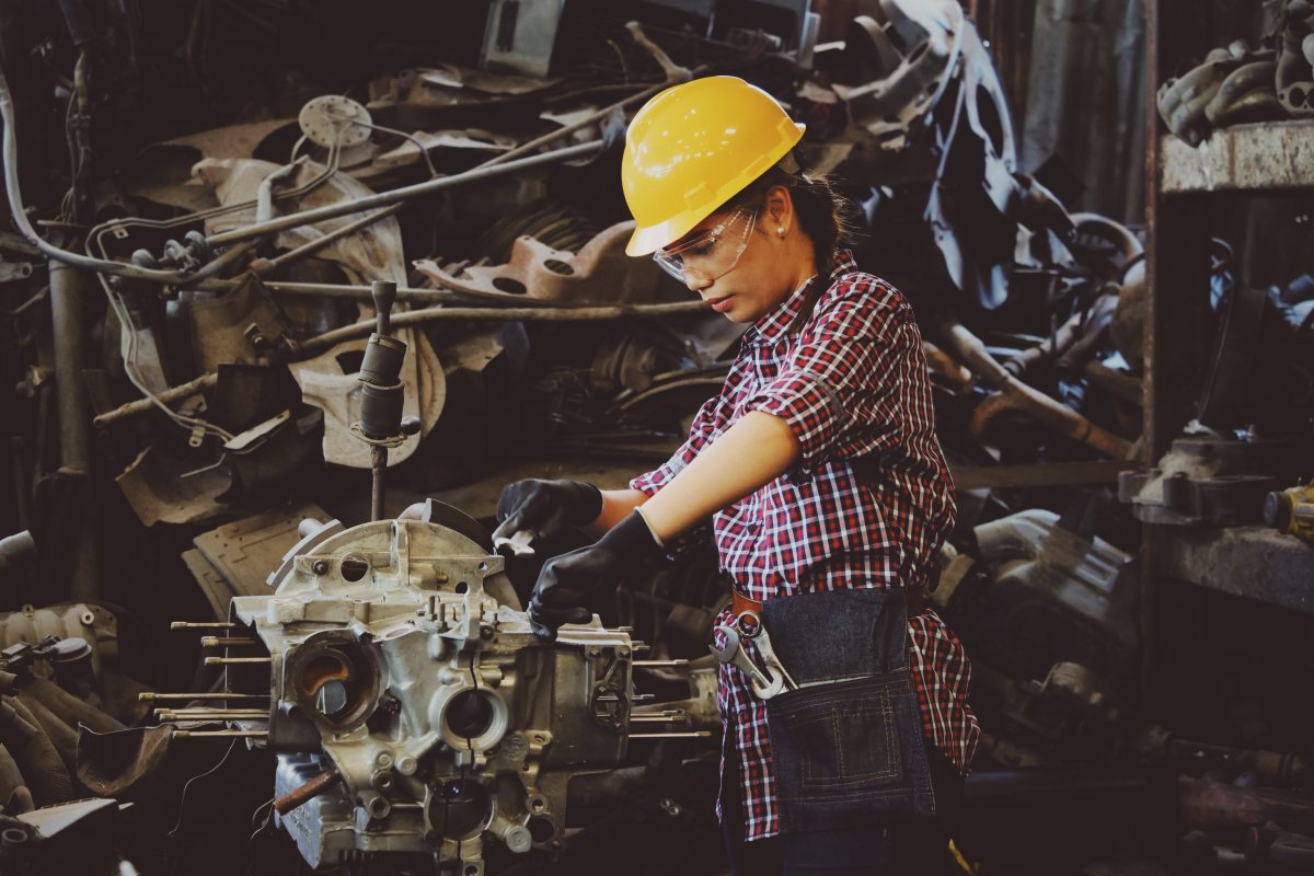 A lady mechanical engineer working on an engine.